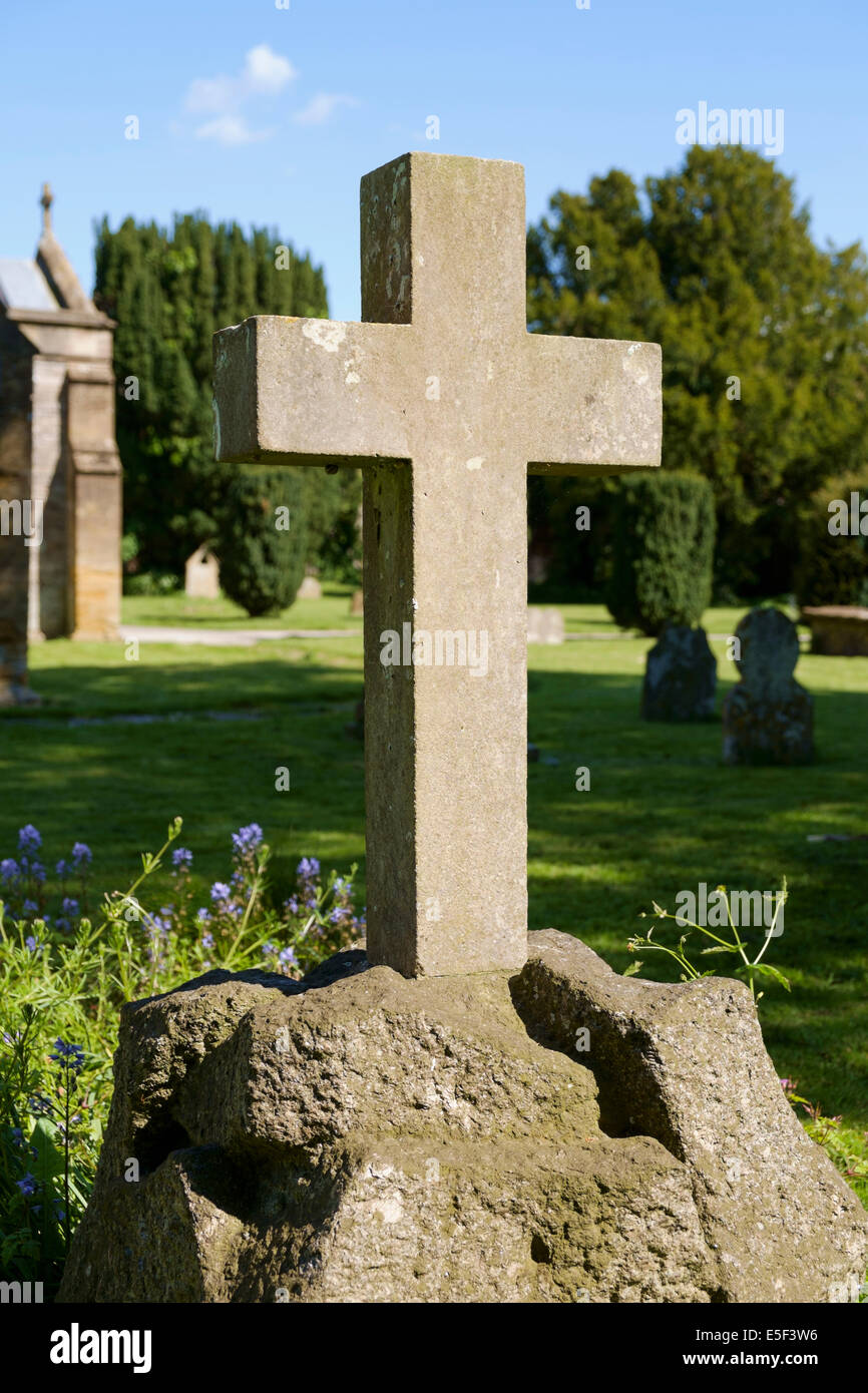 Cross in graveyard on a gravestone in a village churchyard, England, UK - Stock Image