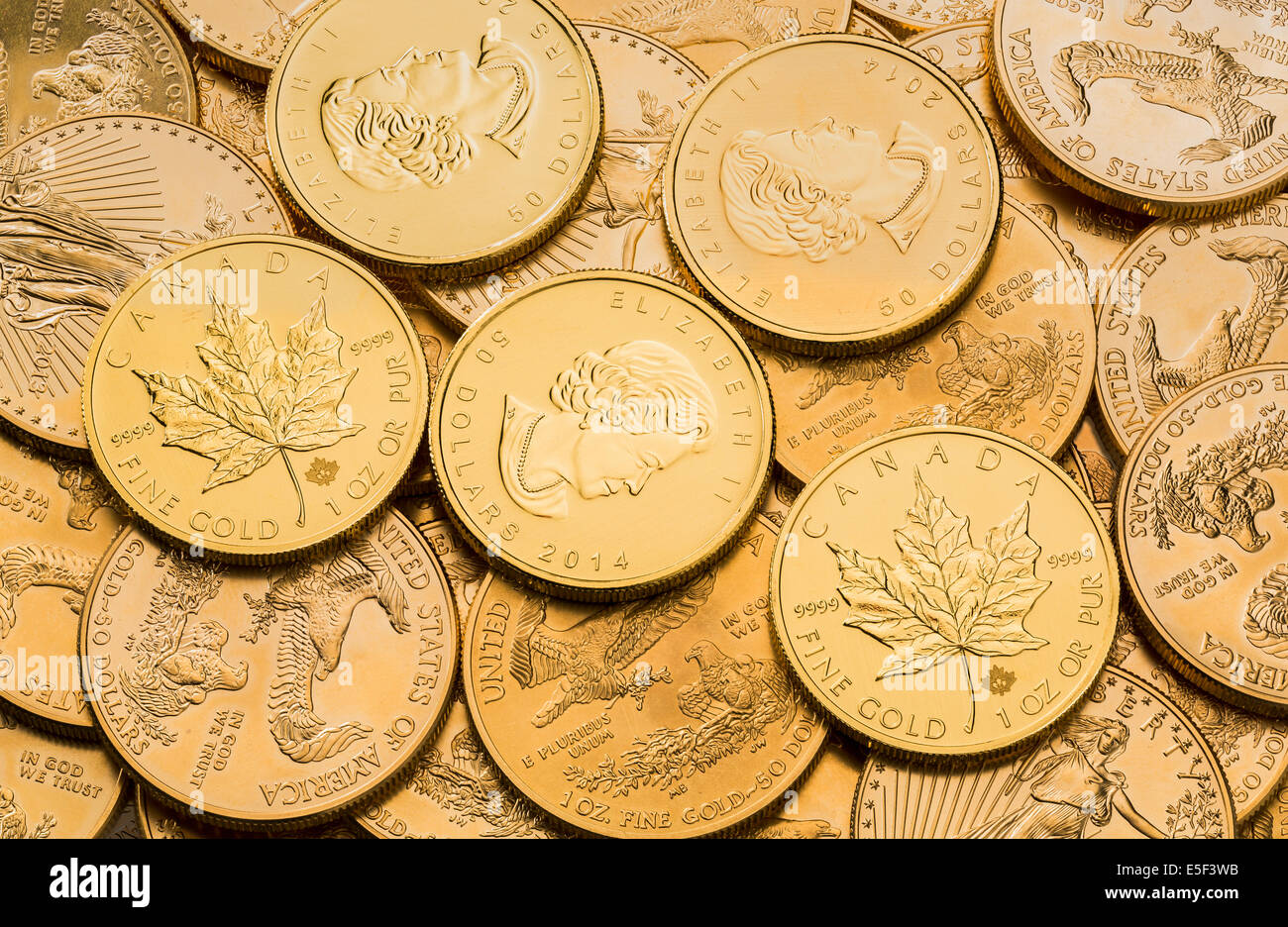 Gold eagle one troy ounce golden coins from US Treasury mint and Canadian Gold Maple Leaf coins - Stock Image