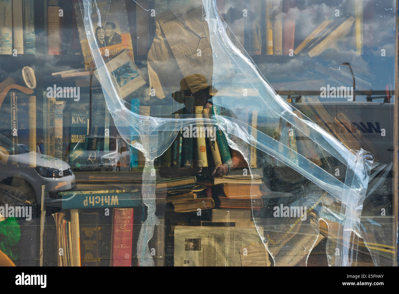 The window display of a scruffy second-hand bookshop - Stock Image
