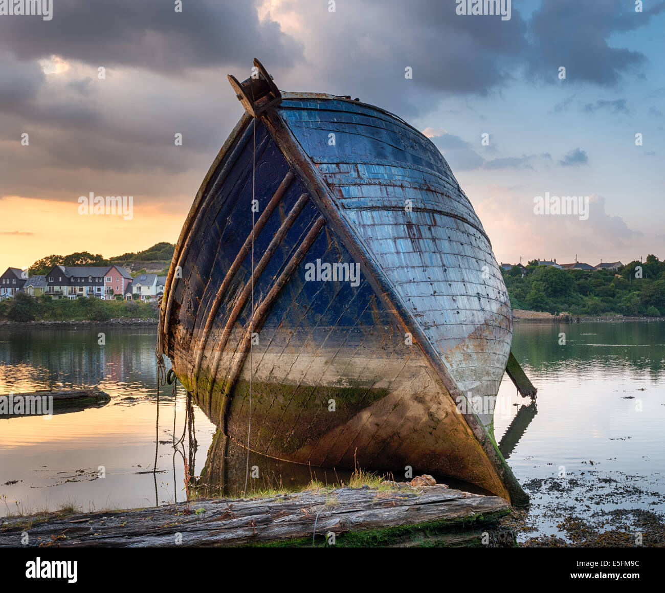 Old abandoned wooden fishing trawler resting on the shore - Stock Image