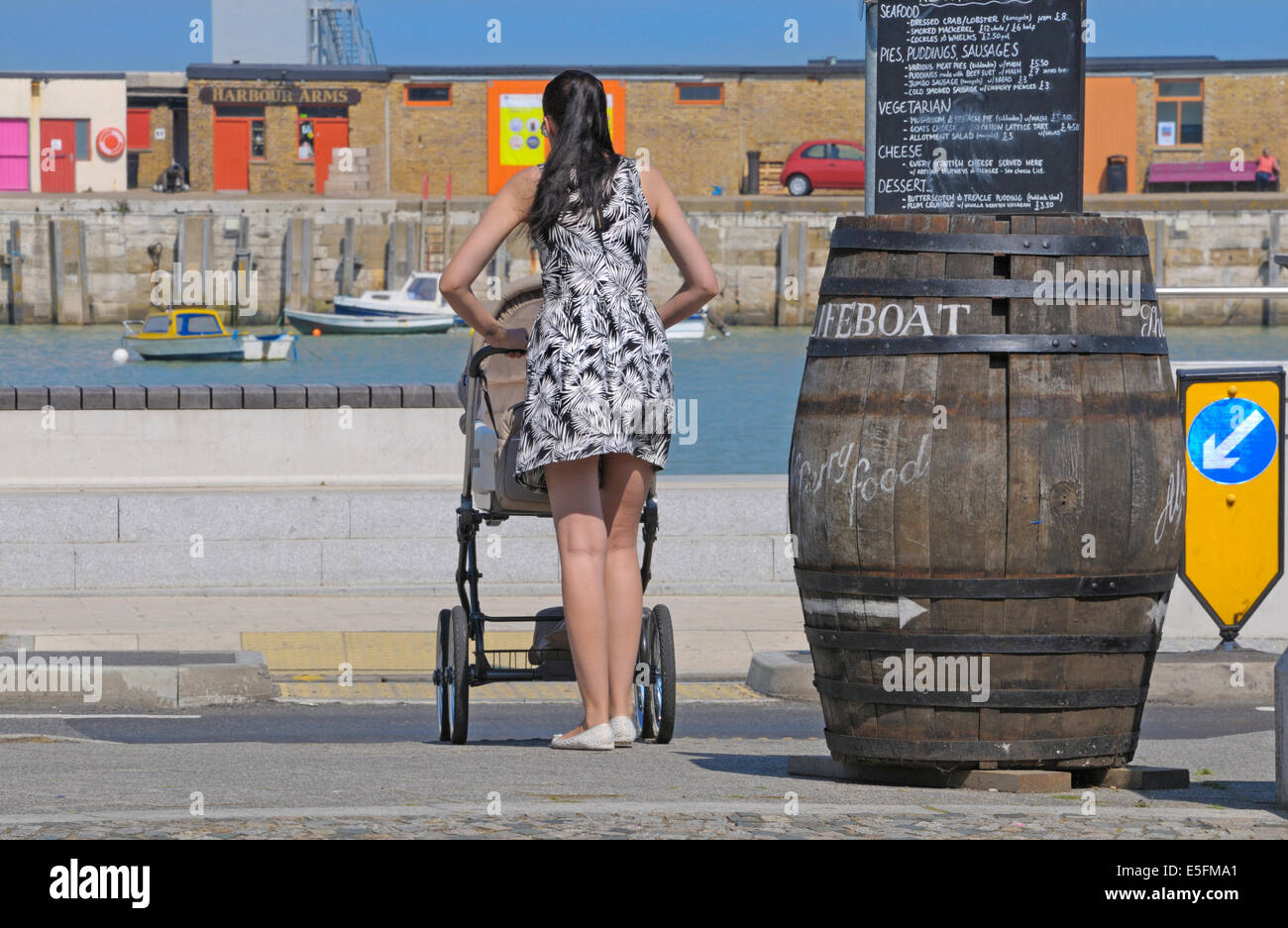 Margate, Kent, England, UK. Young mother with a pushchair waiting to cross the road Stock Photo