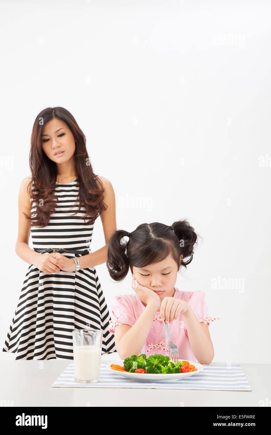 Asian young mother worries her daughter no appetite to eat vegetables - Stock Image