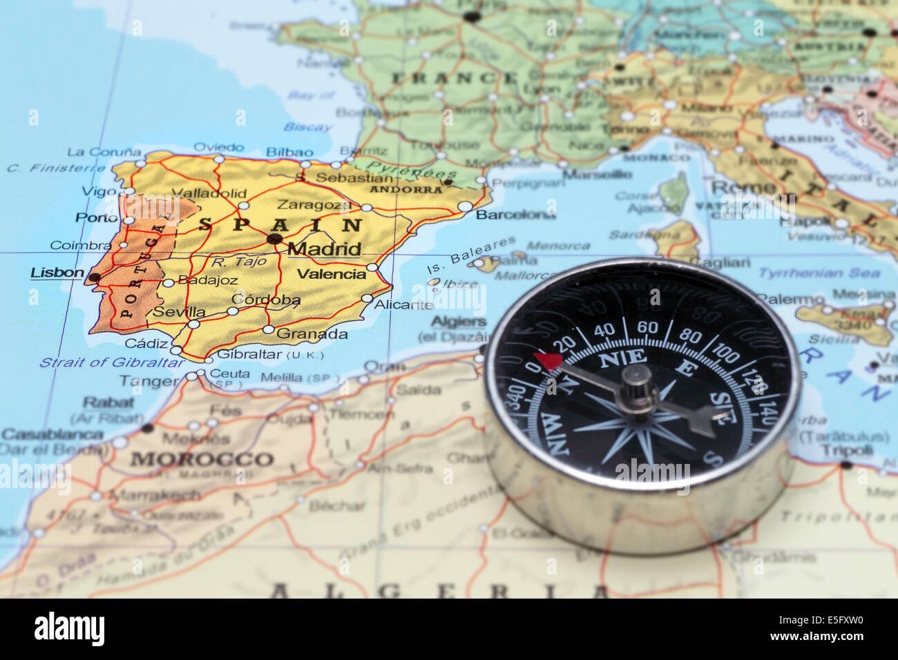 compass on a map pointing at spain and planning a travel destination