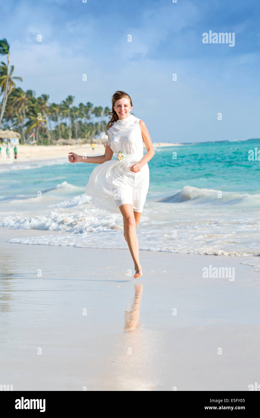 A happy young woman in a white dress running along the sand with a turquoise sea behind, Bavaro, Dominican Republic Stock Photo