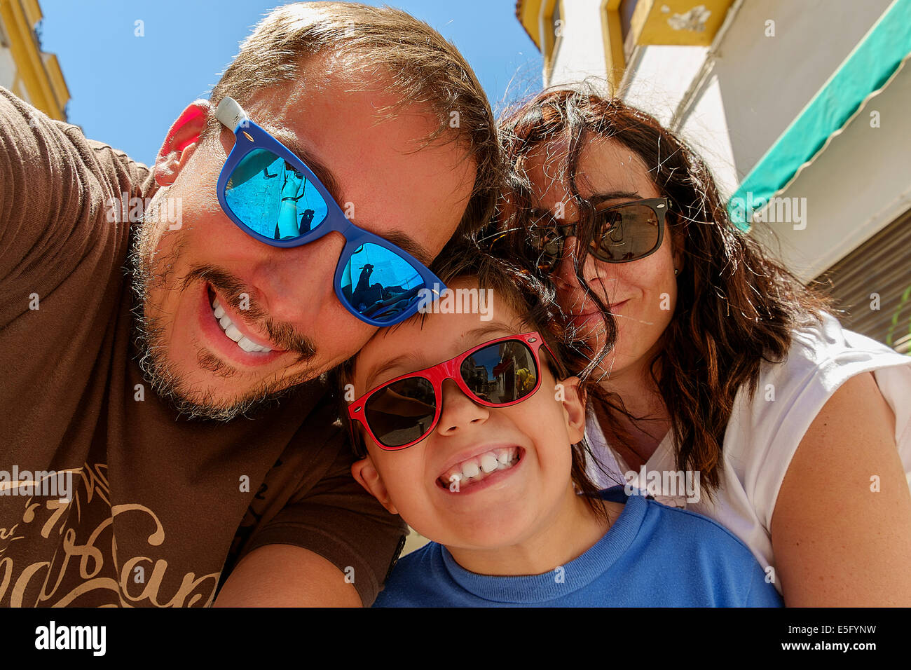 Family having fun wearing sunglasses & waving to a camera taking selfie photograph on summer holiday - Stock Image