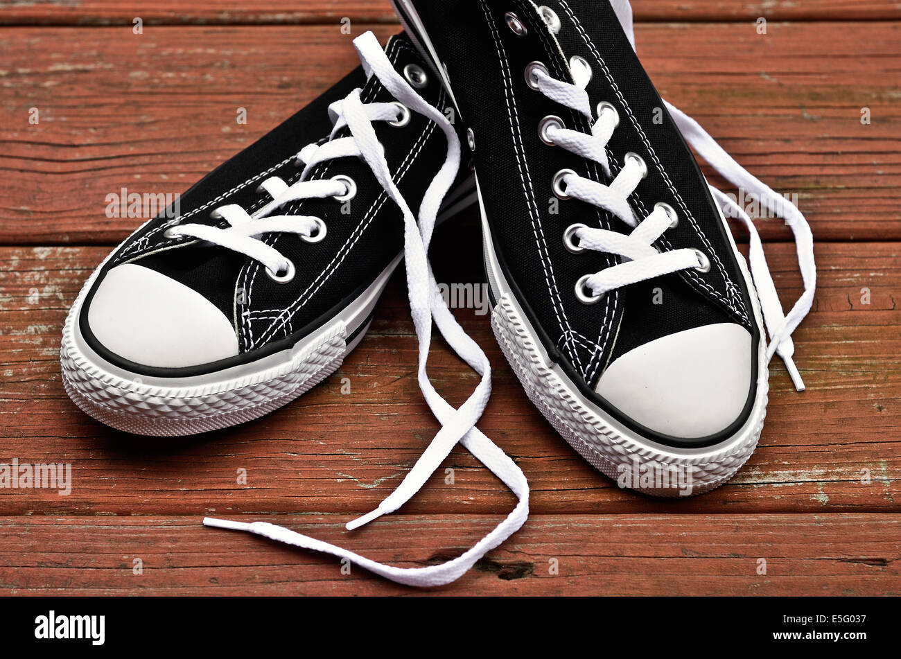 Black and white sneakers on wooden floor - Stock Image