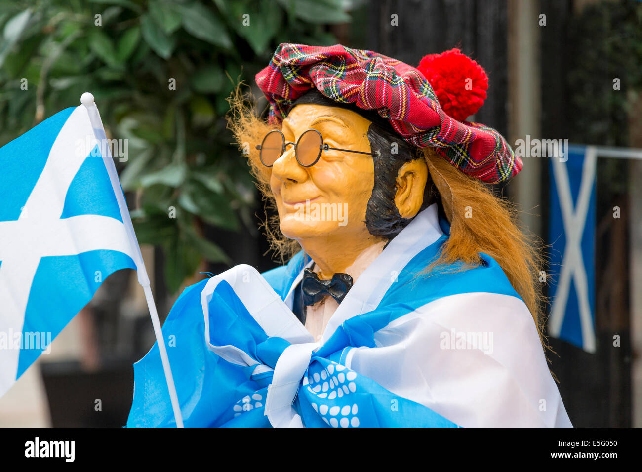 Small mannequin of a man dressed in a tartan hat, covered with a Saltire flag and carrying a small flag, - Stock Image