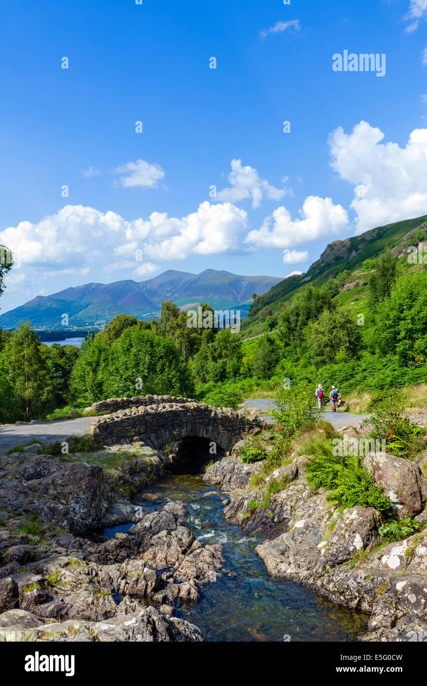Walkers at Ashness Bridge with Skiddaw massif in the distance, Borrowdale, Lake District, Cumbria, UK - Stock Image