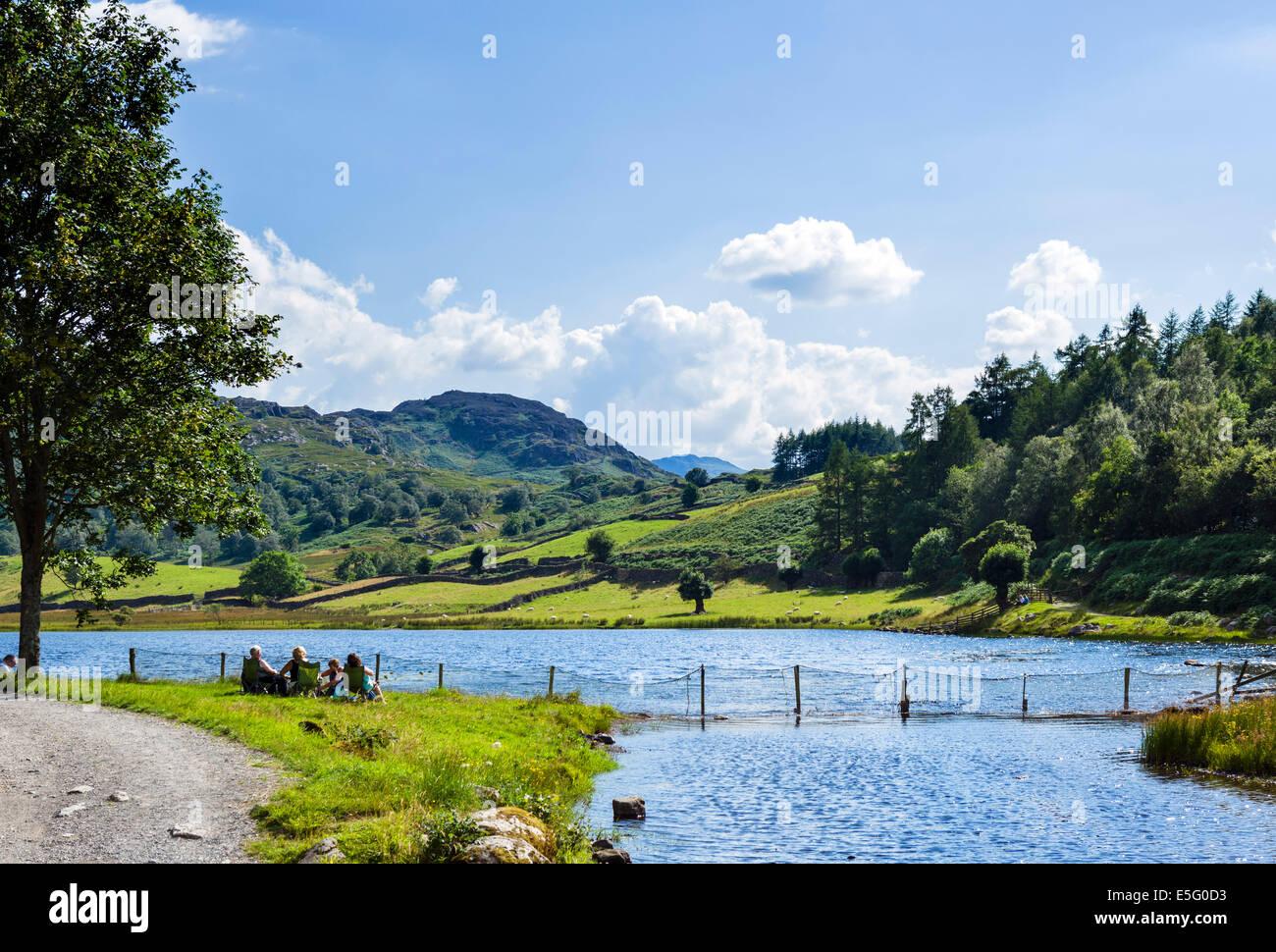 People picnicking by the side of Watendlath Beck, Watendlath Tarn, Borrowdale, Lake District, Cumbria, UK - Stock Image