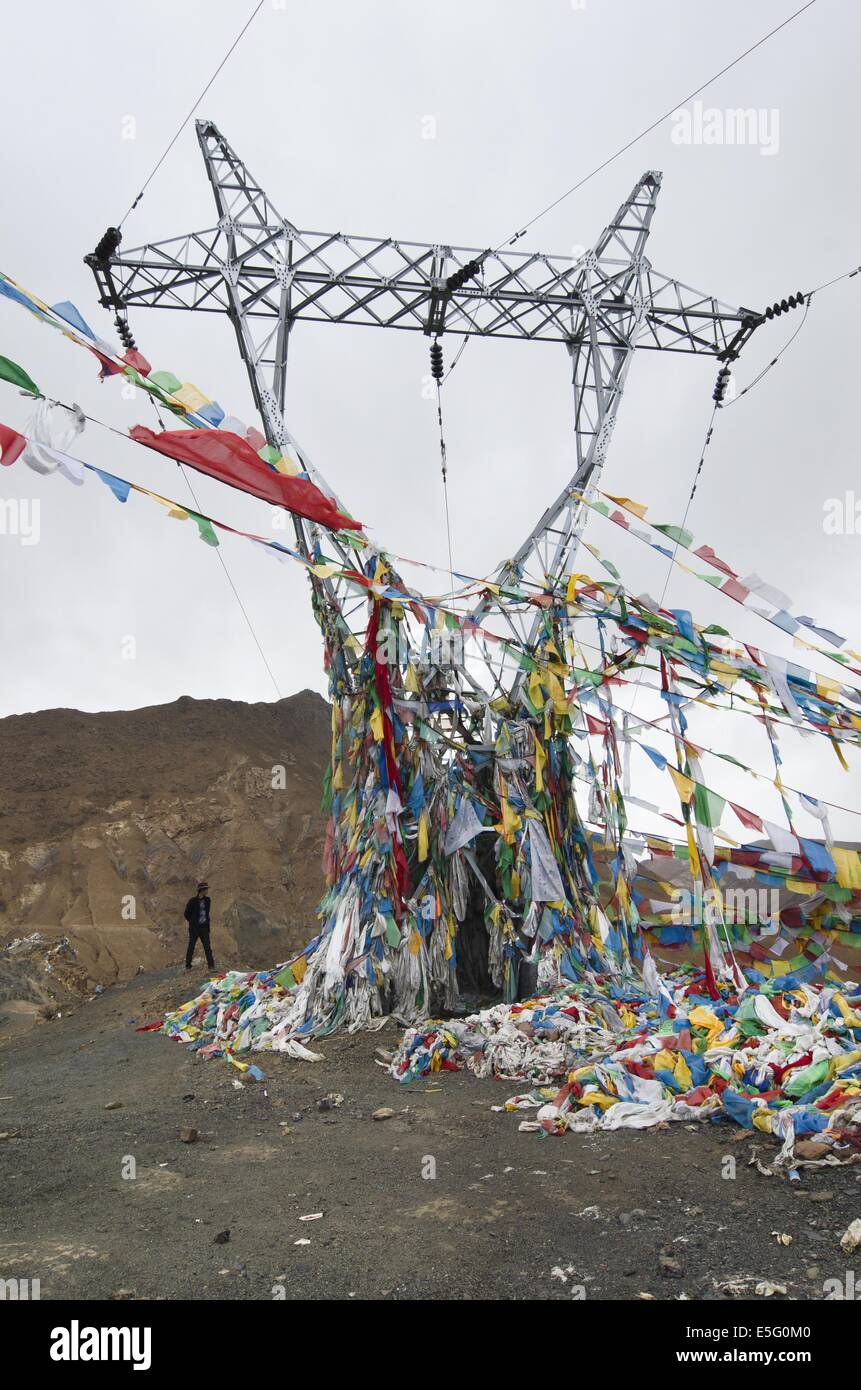 Prayer flags cover an utility pole in Tibet - Stock Image