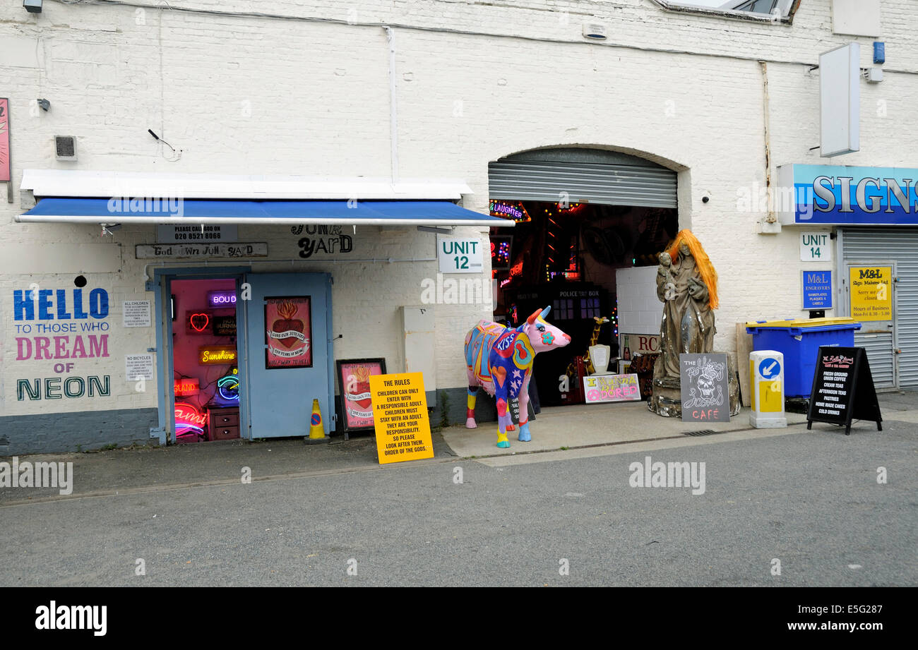 Gods own junkyard neon lighting shop next door to the Rolling Scone Cafe with colourful cow in front Walthamstow, - Stock Image