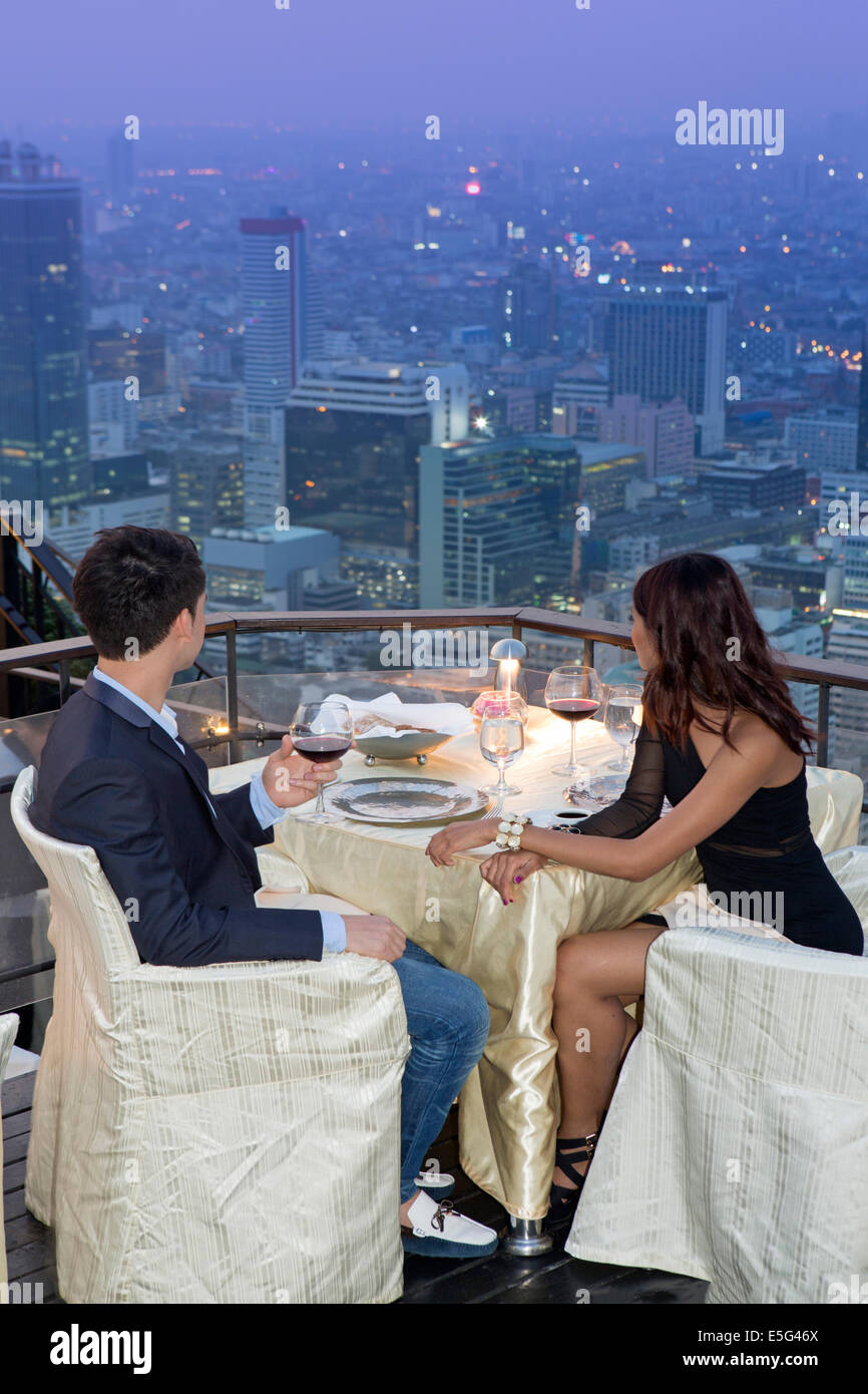 A young couple having dinner at Vertigo restaurant and looking over Bangkok city, Thailand - Stock Image