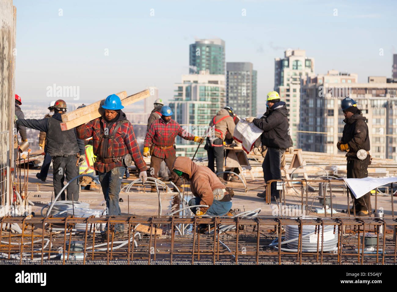 A construction worker carrying a load of lumber with other workers in the background on a rooftop construction site - Stock Image