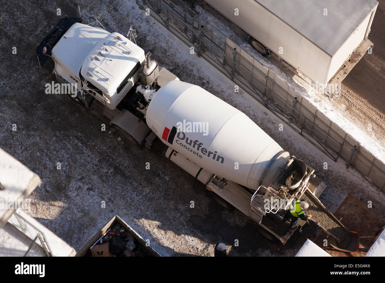 A cement mixer truck dumping a load of fresh concrete with a worker overseeing the operation. Taken from overhead - Stock Image