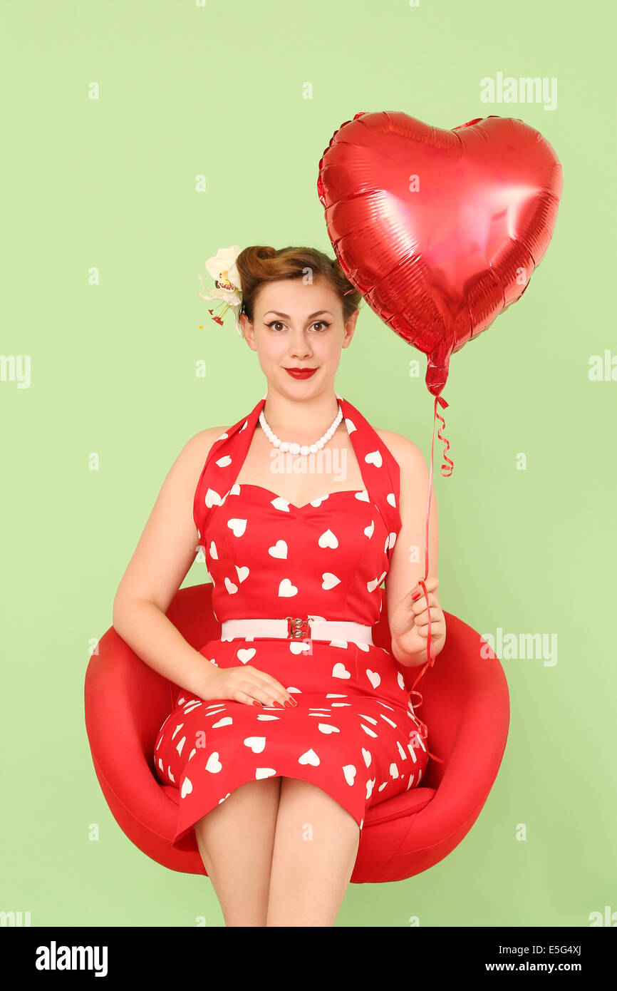 Woman in red dress holding heart shaped balloon Stock Photo
