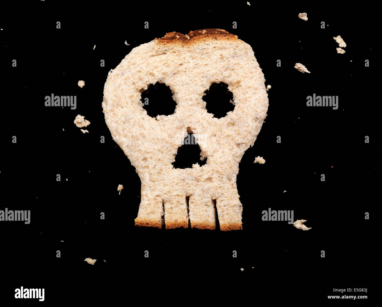 Skull made of bread isolated on black background - Stock Image