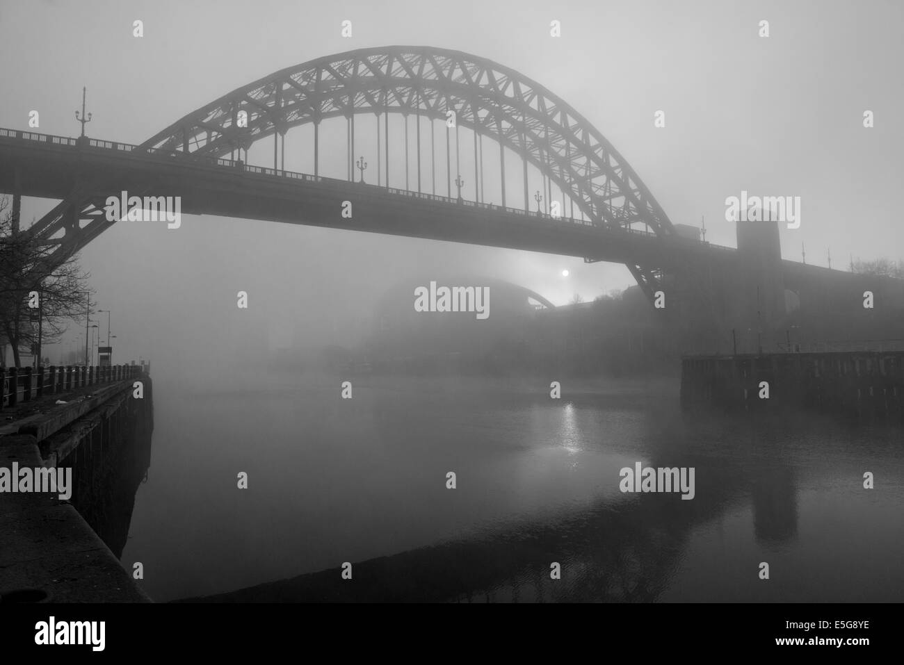 Atmospheric rising sun, between The Sage and the Tyne Bridge, penetrating a fog on the Tyne. - Stock Image
