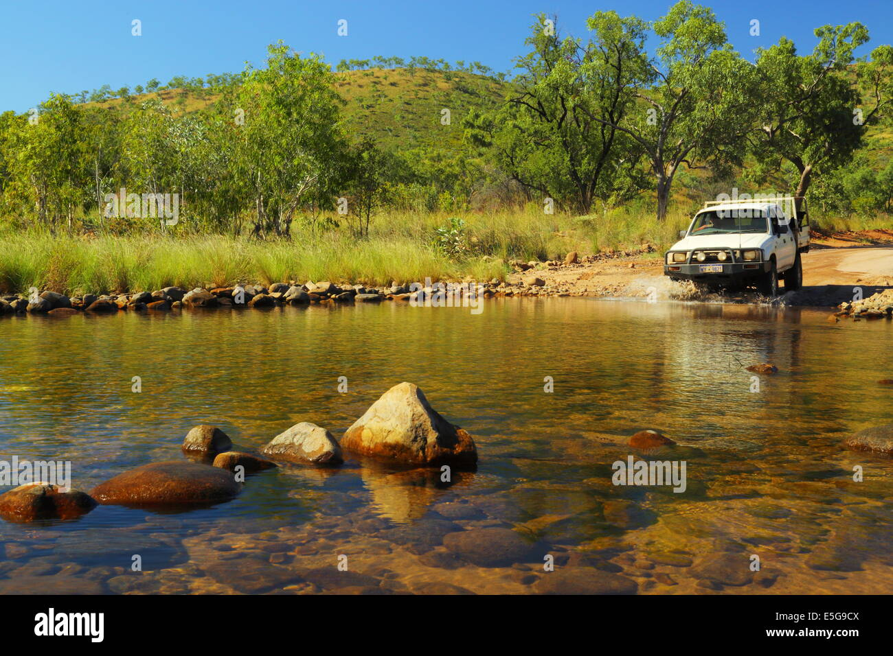 A 4WD vehicle crosses a small stream in the Kimberley region of Western Australia. - Stock Image