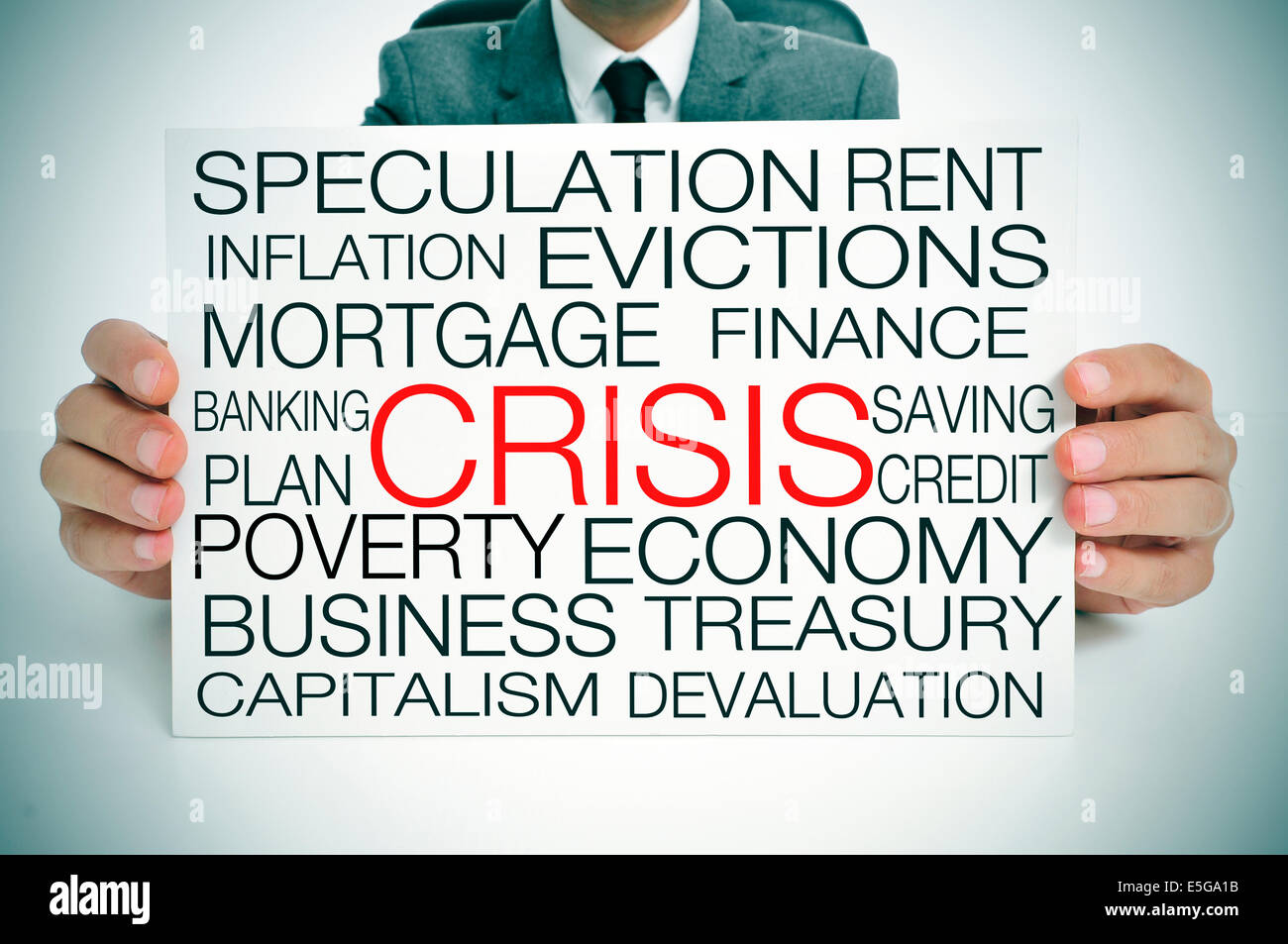 a businessman holding a signboard with different terms related to the economic crisis concept - Stock Image