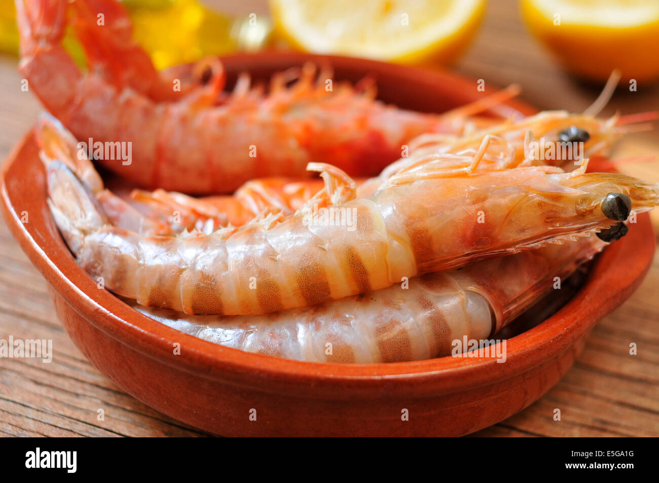 closeup of a earthenware bowl with some fresh raw shrimps on a rustic wooden table - Stock Image