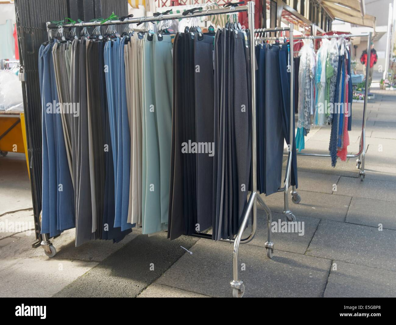 Skirts of many sizes for sale on a rack in the market - Stock Image