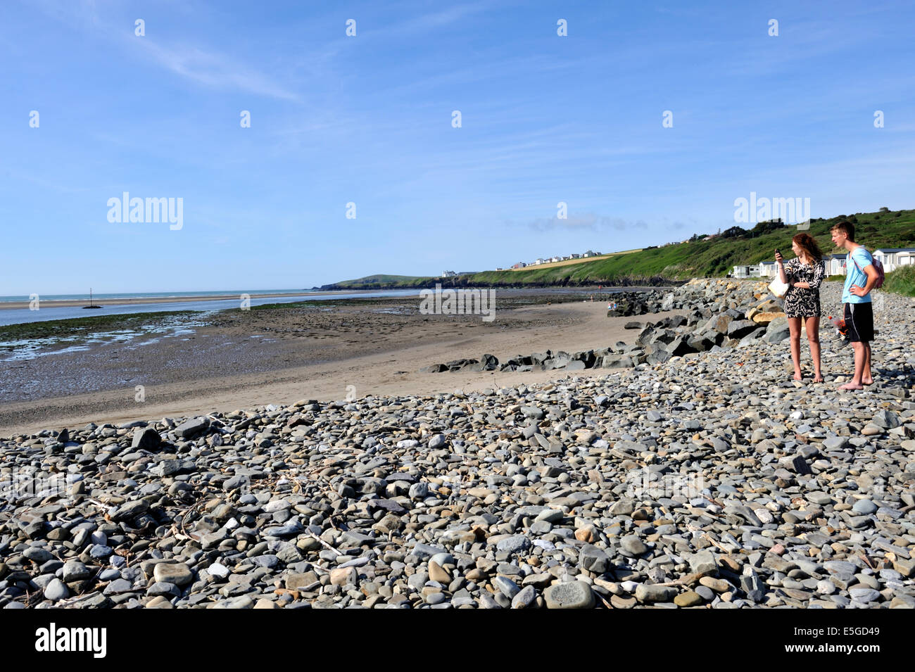 Young couple looking over the cobbled Traeth beach by the Patch Caravan Park, Gwbert, Pembrokeshire Stock Photo