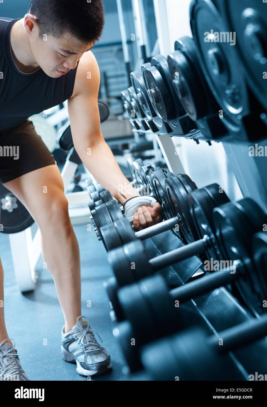 asian man choosing dumbbell in health club - Stock Image