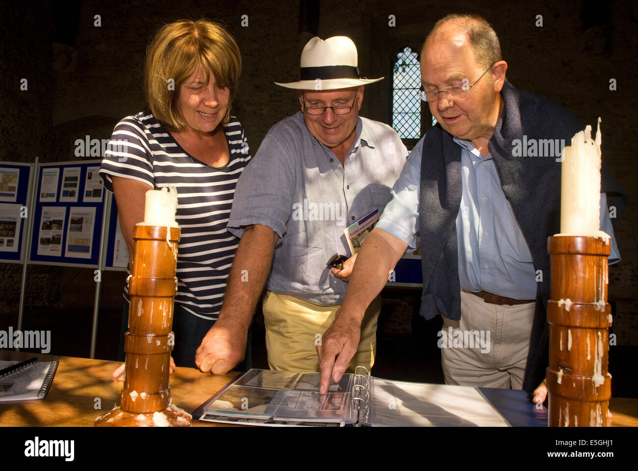 Organiser of a local history exhibition (far right) explaining the history of the local courthouse to visitors, - Stock Image