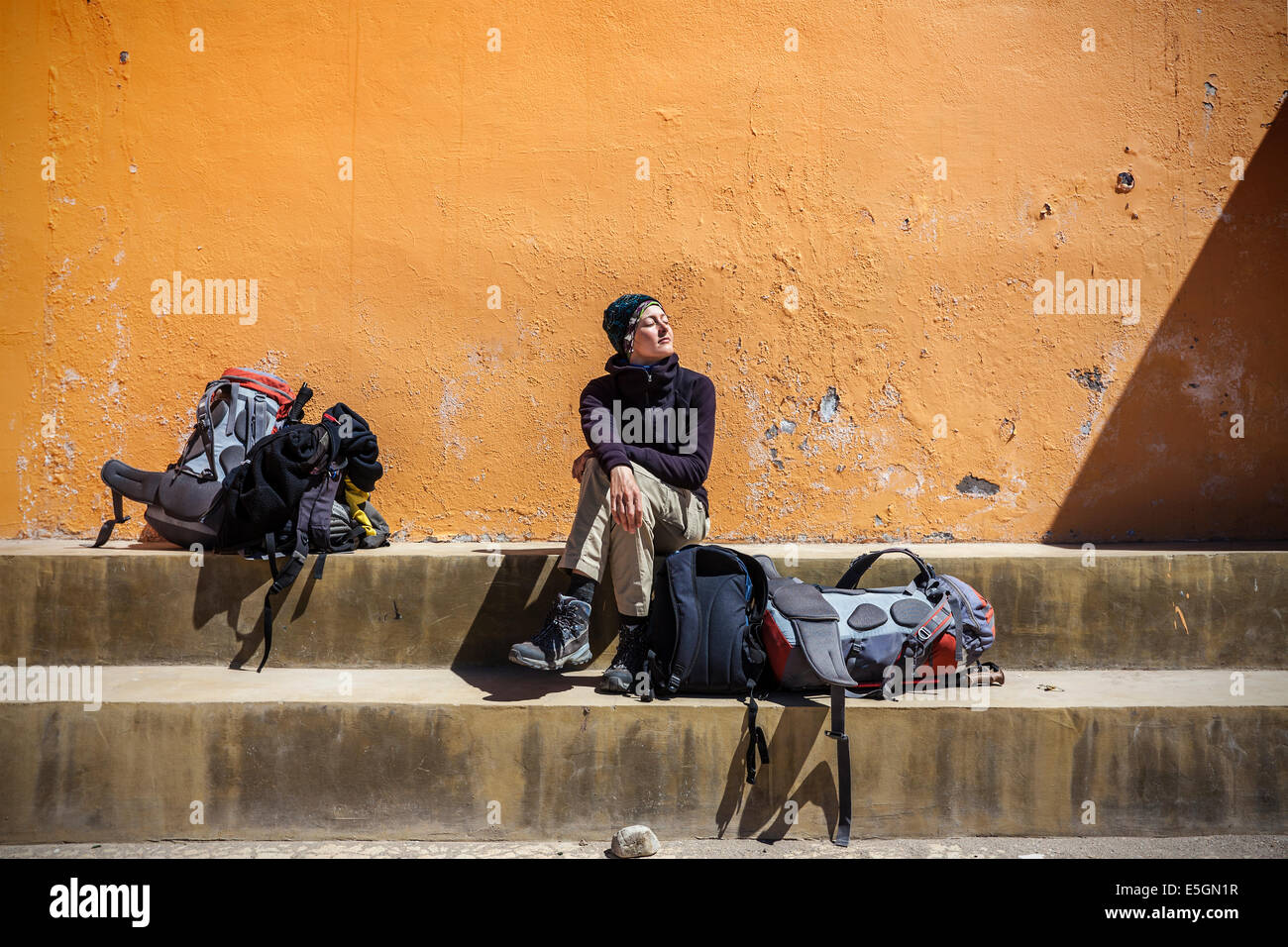 Girl waiting with backpacks in sun. - Stock Image