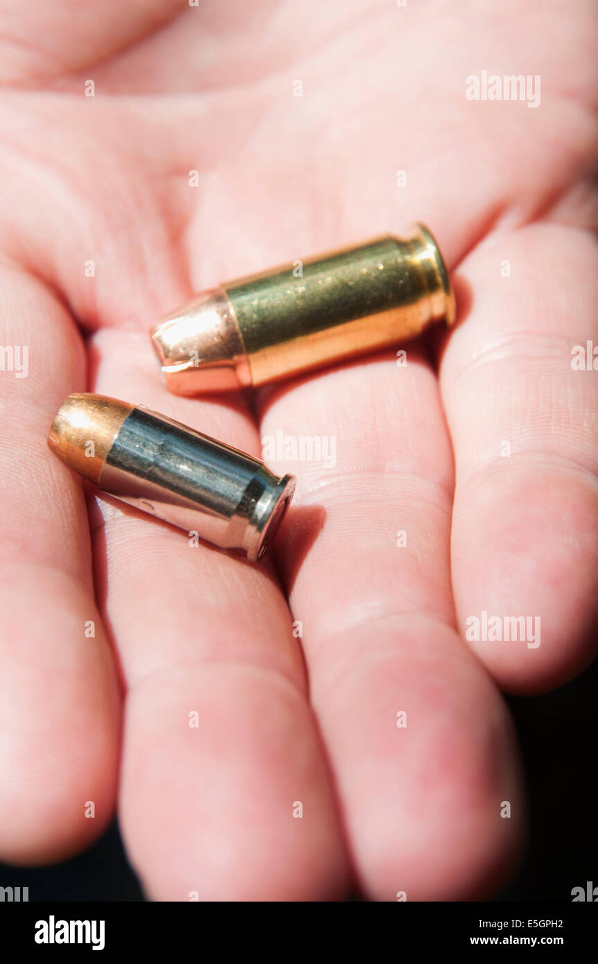 A hand holding two bullets. - Stock Image