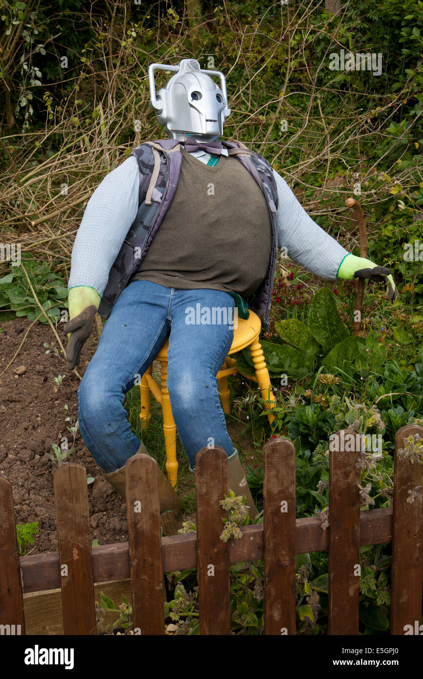 Scarecrow with cyberman head sat on chair in English garden - Stock Image