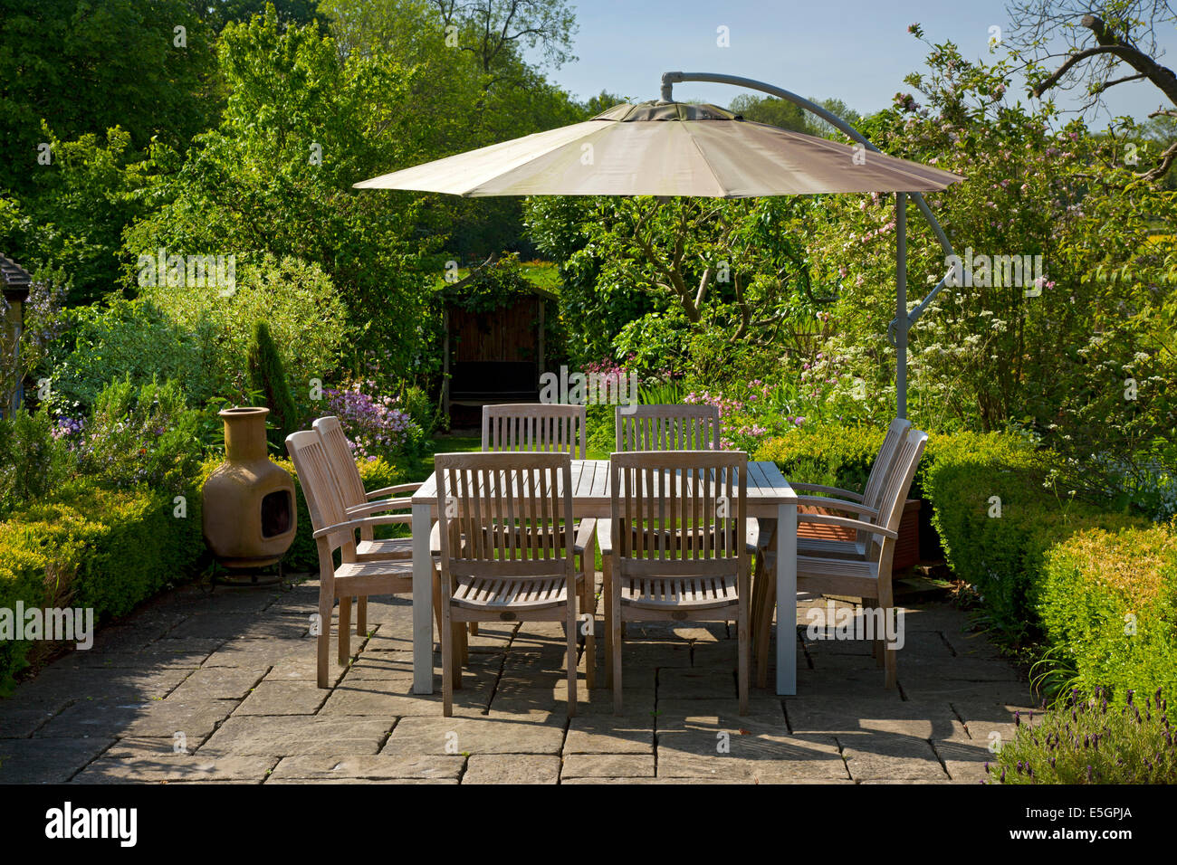 Outdoor eating area with table and chairs in English summer garden - Stock Image