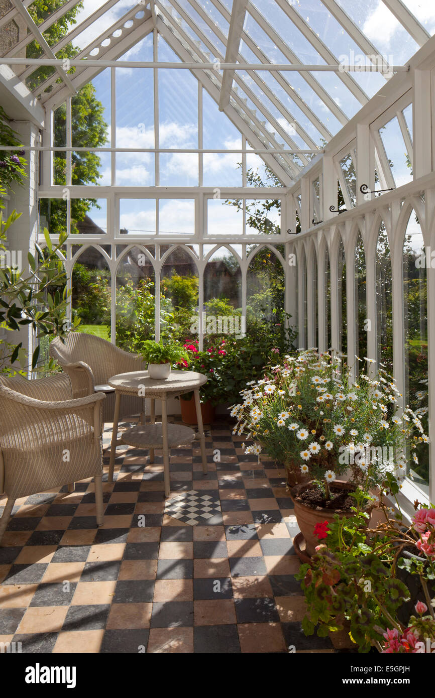 Interior of old style English wooden conservatory with wicker seating and flower pots - Stock Image