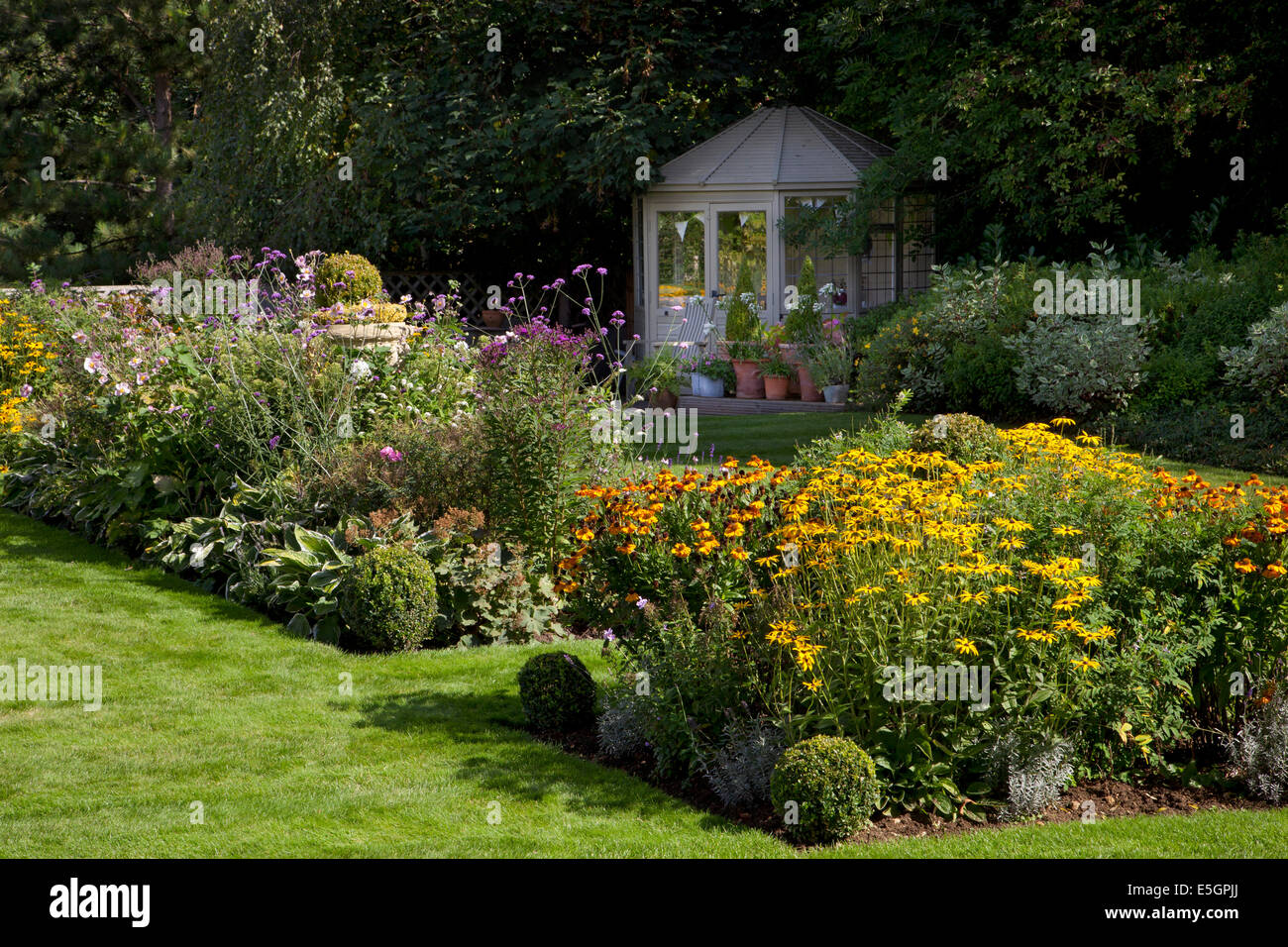 Wooden Summerhouse with colourful late summer flower boarders in English garden,Oxfordshire,England - Stock Image