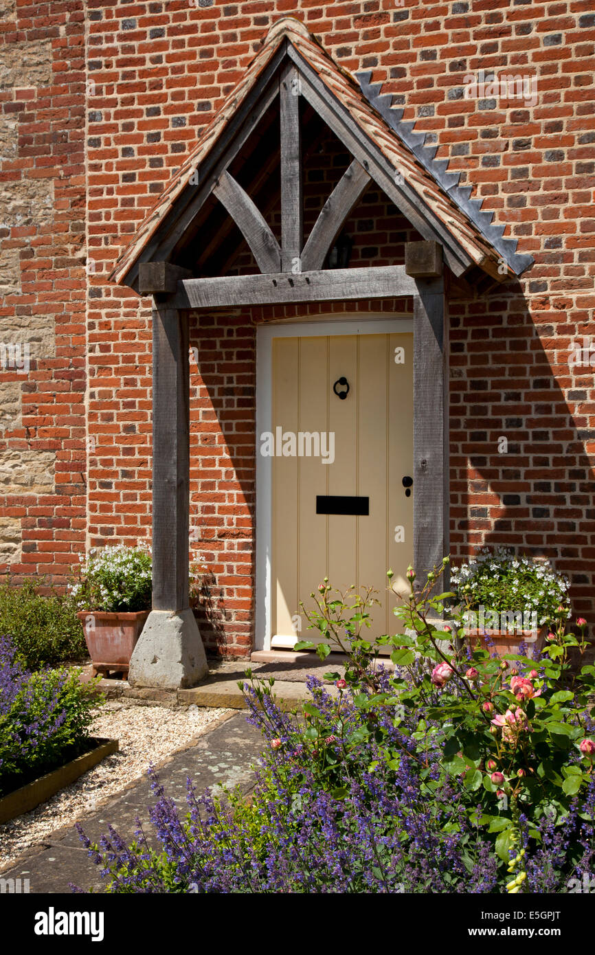 Front porch and doorway of English farmhouse with path and cottage garden - Stock Image