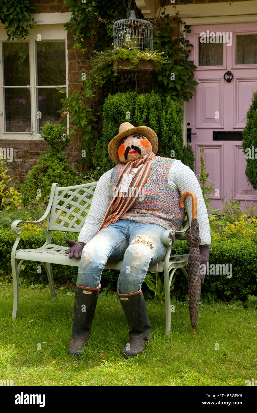 Scarecrow sat on bench outside house in England - Stock Image