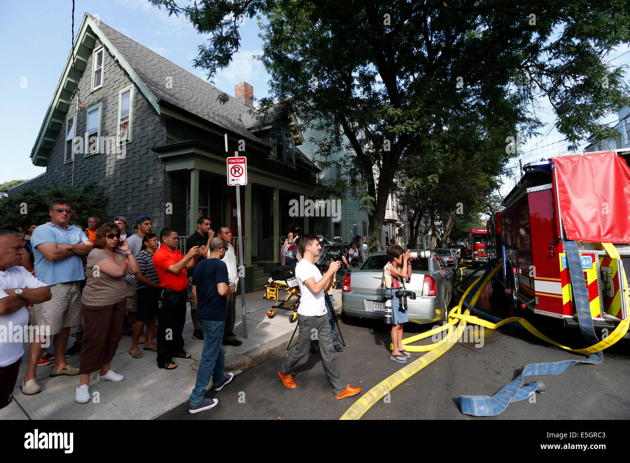 People gather to watch firefighters responding to a 6-alarm house fire in Boston, Massachusetts USA - Stock Image