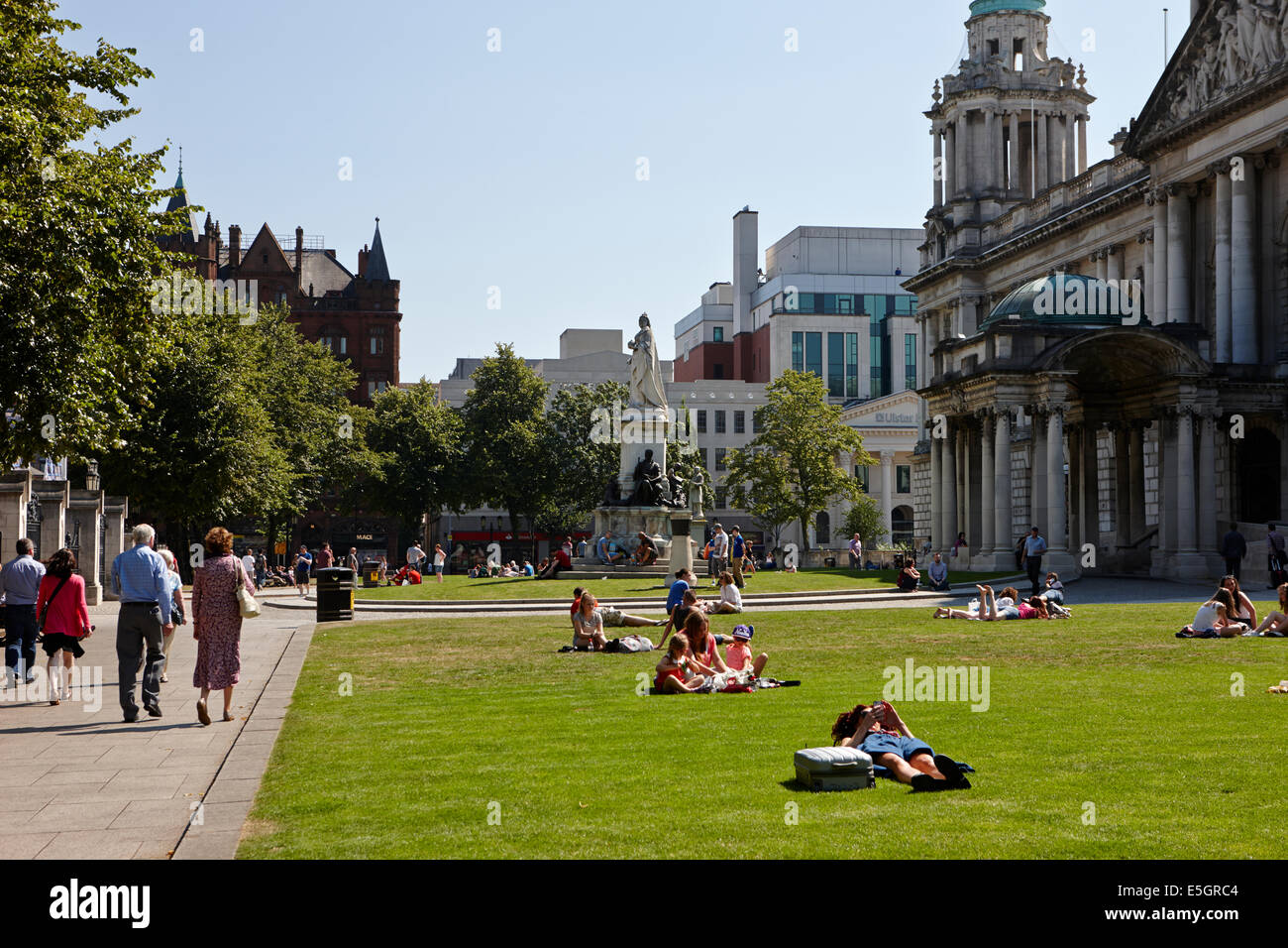people enjoying hot summers day in the grounds of Belfast city hall in the city centre - Stock Image