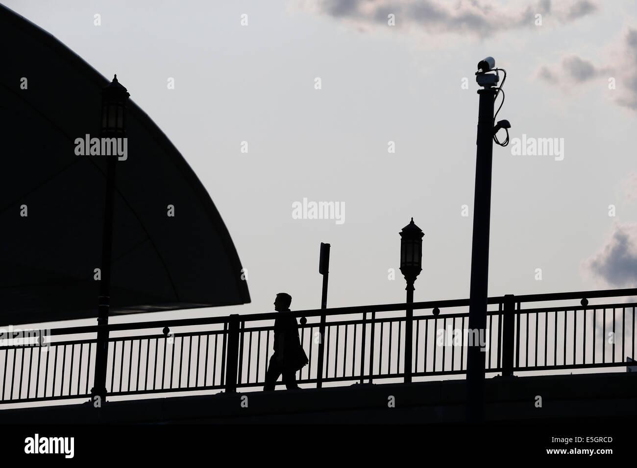 A pedestrian in silhouette walks under a pole mounted surveillance camera. Boston, Massachusetts, USA - Stock Image