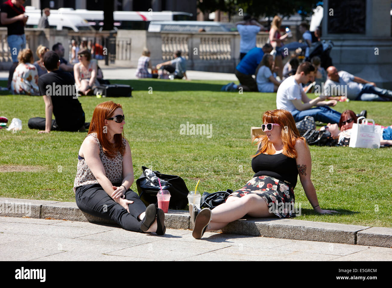 two red headed women enjoying cool drink on hot summers day in the grounds of Belfast city hall in the city centre - Stock Image