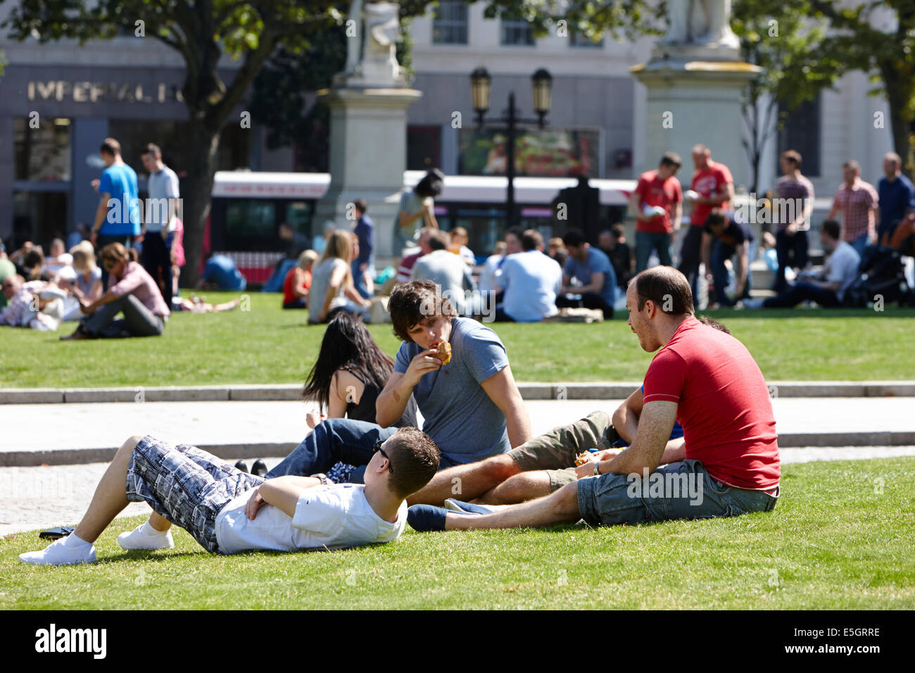 people having lunch enjoying hot summers day in the grounds of Belfast city hall in the city centre - Stock Image
