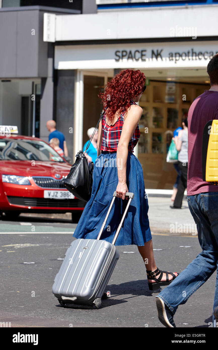 red haired young woman with wheeled suitcase walking across the road in Belfast city centre - Stock Image