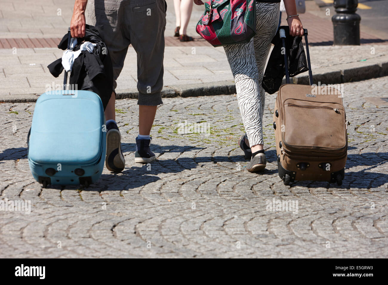 two women with wheeled suitcases walking across the road in Belfast city centre - Stock Image