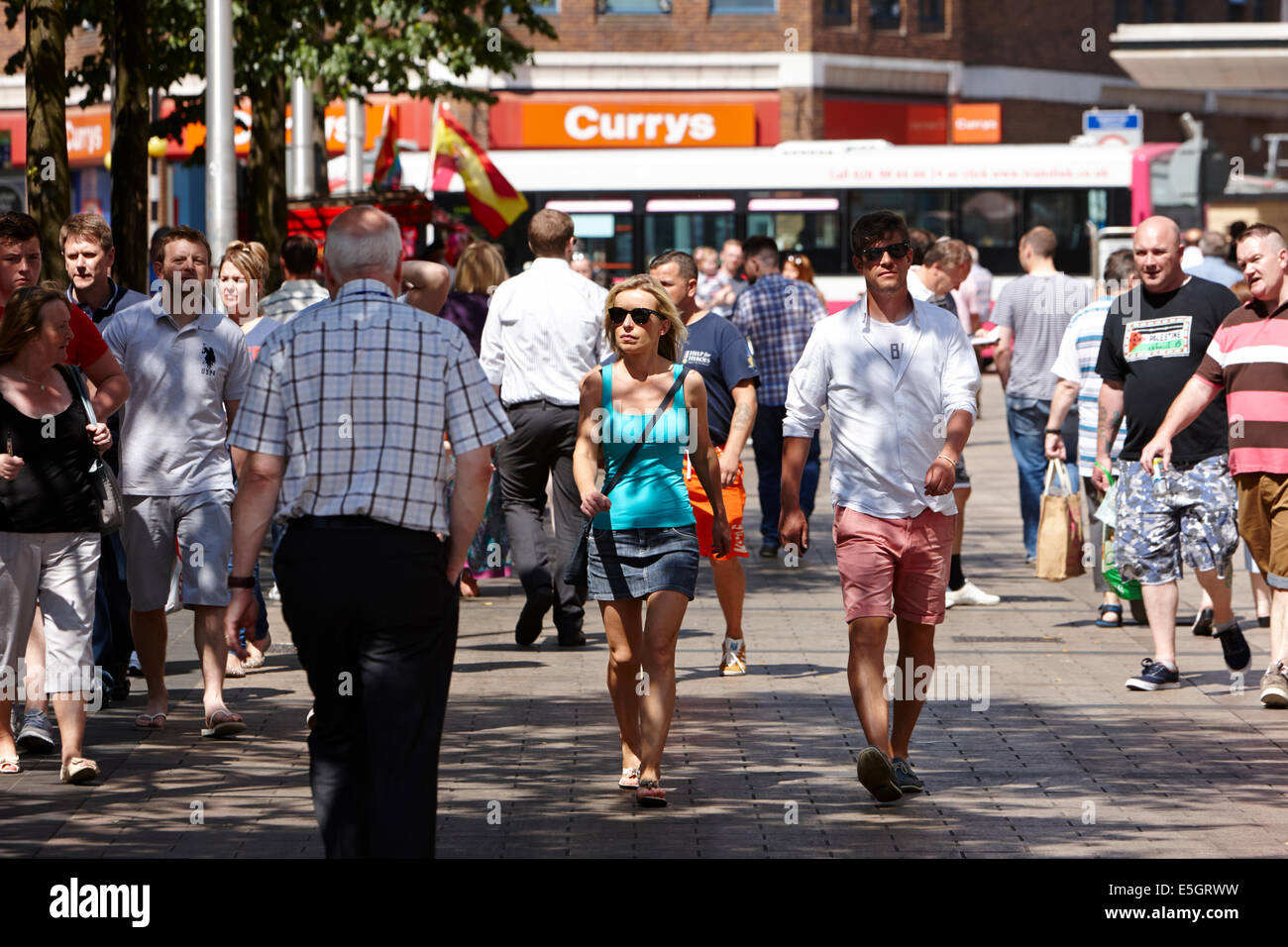 people walking through busy cornmarket on a hot sunny day in Belfast city centre - Stock Image