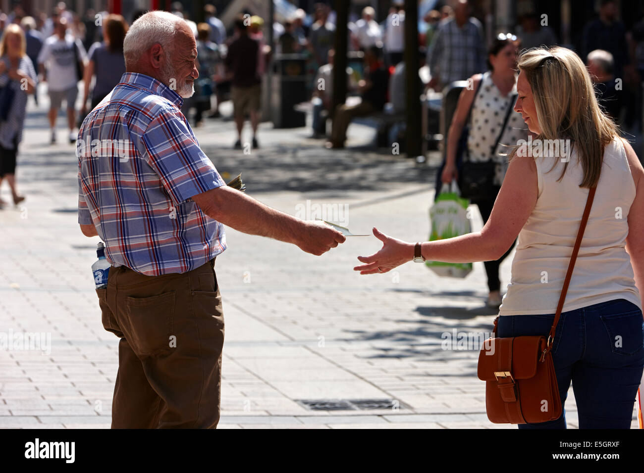 religious preacher handing out leaflets to woman in Belfast city centre - Stock Image