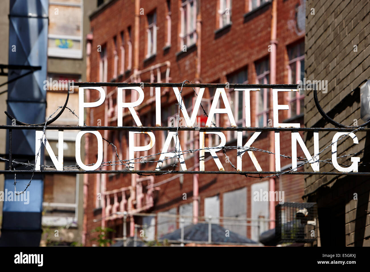 private no parking sign wrapped in barbed wire in a city centre in the uk - Stock Image