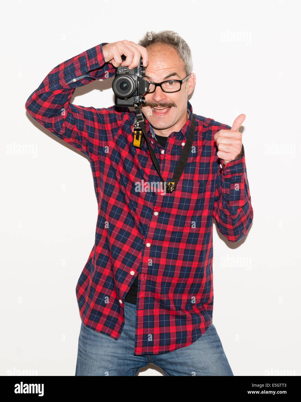 Photographer guy with moustache wearing checked shirt holding a camera and taking a picture while giving thumbs - Stock Image