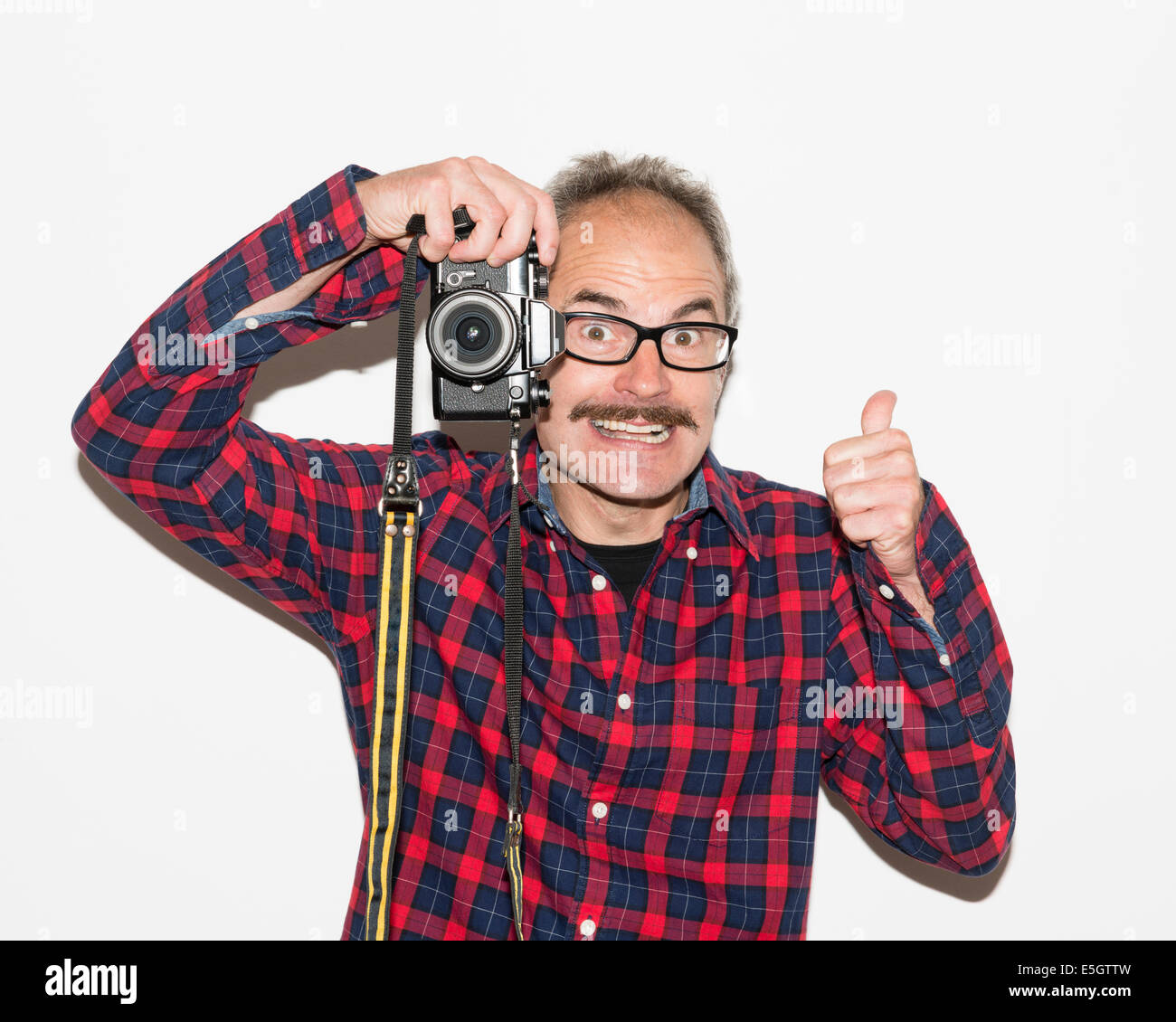 Fashion photographer guy with moustache, glasses, plaid shirt giving thumbs up and taking a picture with retro camera. - Stock Image
