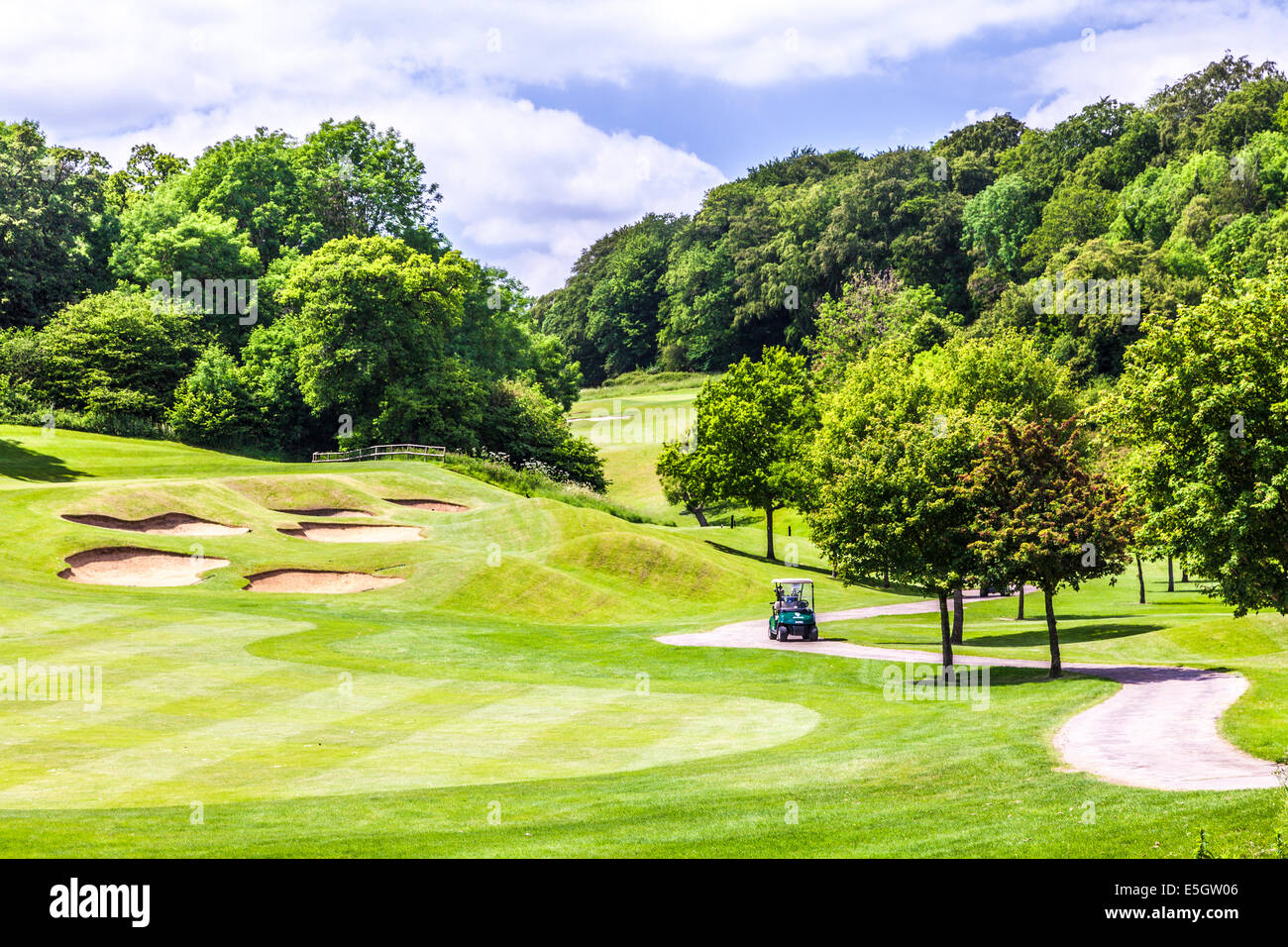 Bunkers, putting green and buggy on a typical golf course. - Stock Image
