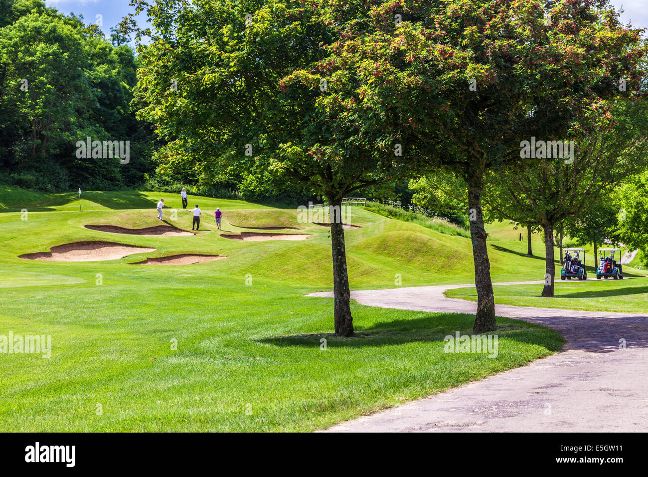 Four male golfers playing near bunkers on a golf course. - Stock Image